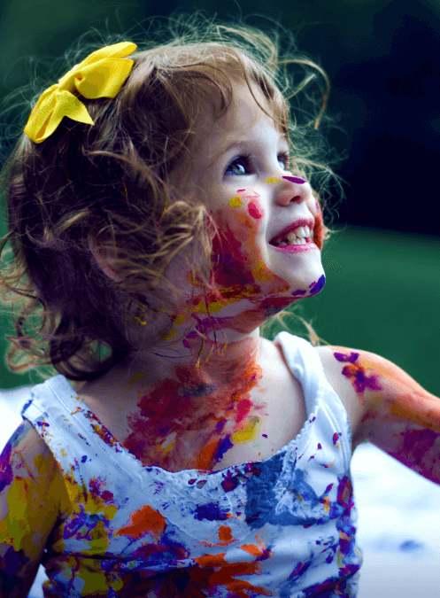 Criança sorrindo brincando com tinta